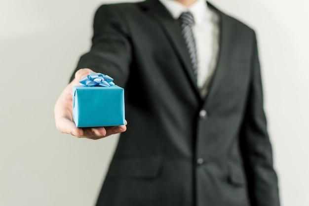 Mann in einem anzug, der eine blaue kleine geschenkbox hält Kostenlose Fotos