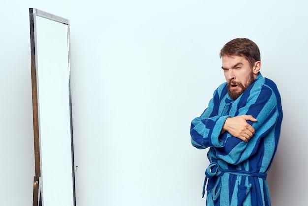 Mann in einem blauen gewand untersucht sich in einem spiegel Premium Fotos