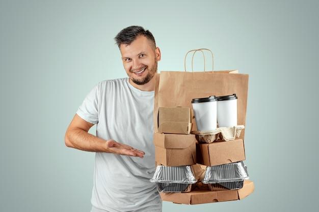 Mann in einem hellen t-shirt, das eine schnellimbissbestellung lokalisiert auf einem blauen hintergrund gibt Premium Fotos
