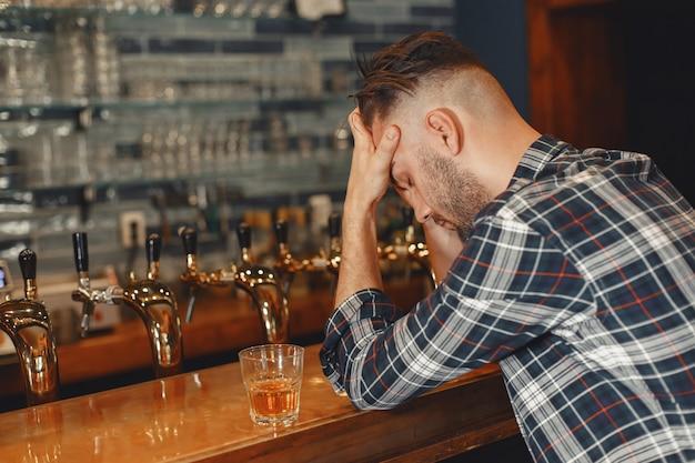 Mann in einem hemd hält ein glas in seinen händen. guy sitzt an der bar und hält seinen kopf. Kostenlose Fotos