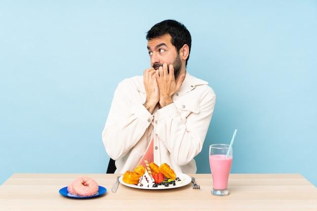 Mann in einem tisch mit essen, das eine seite betrachtet Premium Fotos
