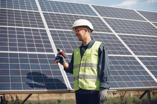 Mann in einem weißen helm nahe einem sonnenkollektor Kostenlose Fotos