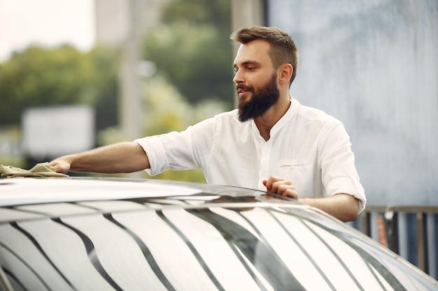 Mann in einem weißen hemd wischt ein auto in einer autowäsche ab Kostenlose Fotos