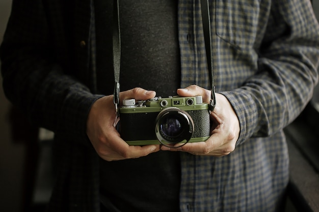 Mann in hemdmannhänden hält filmgrünkamera retro horizontal Premium Fotos