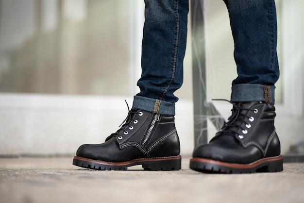 Mann in jeans und schwarzen lederstiefeln Premium Fotos