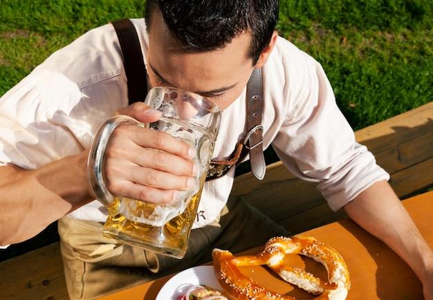 Mann in lederhosen trinkt bier Premium Fotos