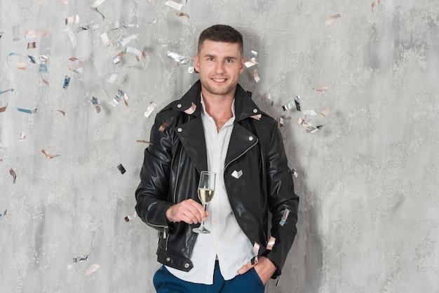 Mann in lederjacke mit champagner Kostenlose Fotos