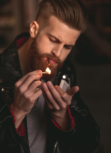 Mann in lederjacke zündet sich eine zigarette an. Premium Fotos