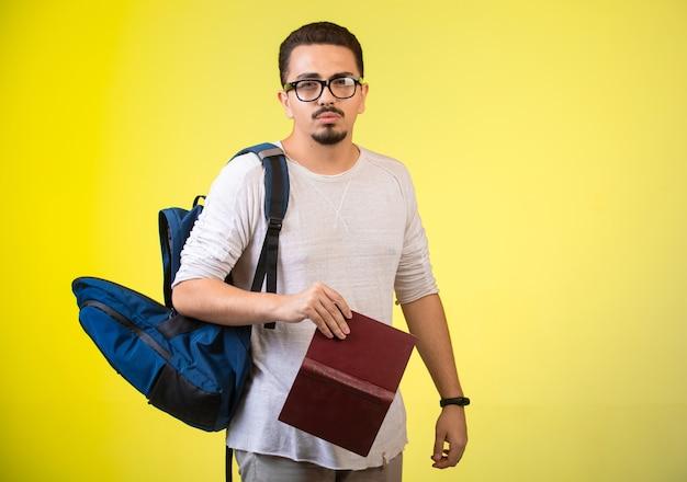 Mann in optischen gläsern, die ein buch halten. Kostenlose Fotos
