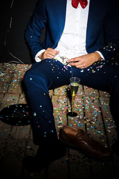 Mann in smoking in der nähe von glas und stiefel zwischen konfetti Kostenlose Fotos