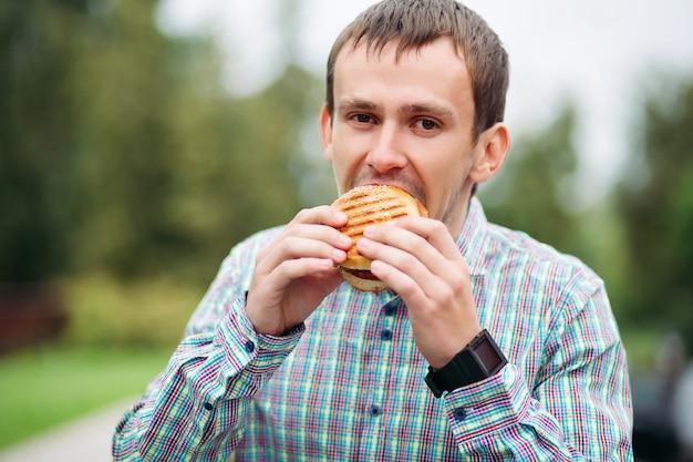Mann in überprüftem hemd leckeren burger draußen essend. Premium Fotos