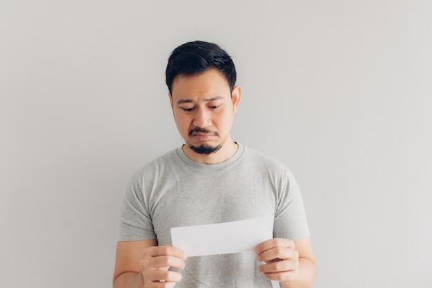 Mann ist hass und traurig mit der weißen postnachricht oder der rechnung. Premium Fotos