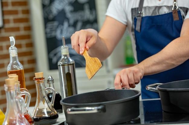 Mann kocht fleisch in einer pfanne. hand mit spatel umrühren bratpfanne voller fleisch. Premium Fotos
