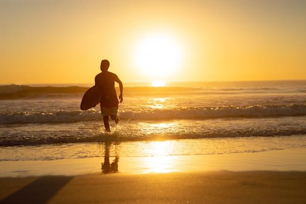 Mann läuft mit surfbrett am strand Kostenlose Fotos