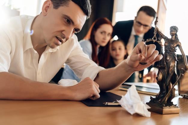 Mann legt verlobungsring auf die waage der figur von themis. Premium Fotos