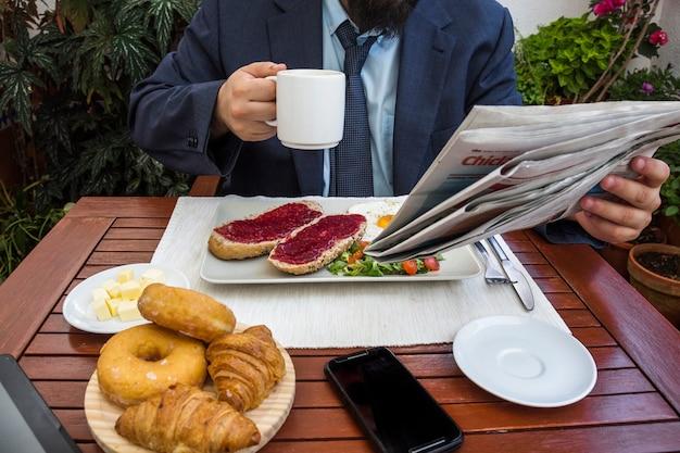 Mann liest zeitung beim frühstücken Kostenlose Fotos