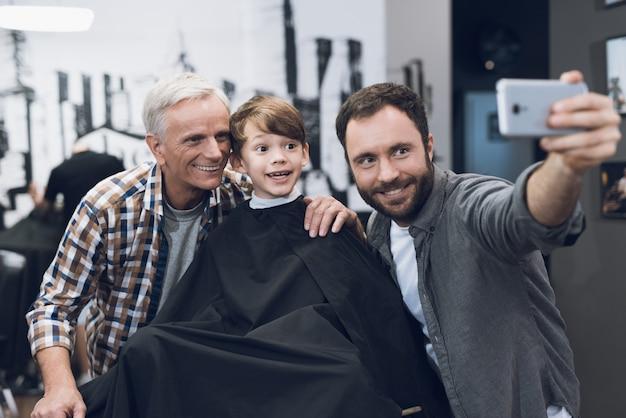 Mann macht selfie auf smartphone mit älterem mann und jungen. Premium Fotos