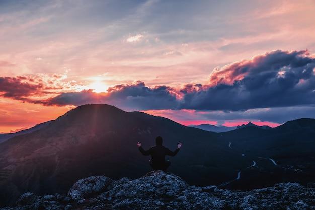 Mann meditiert in den bergen bei sonnenuntergang. Premium Fotos