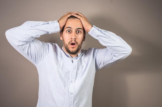 Mann mit ausdruck der verwunderung und den händen auf dem kopf Premium Fotos