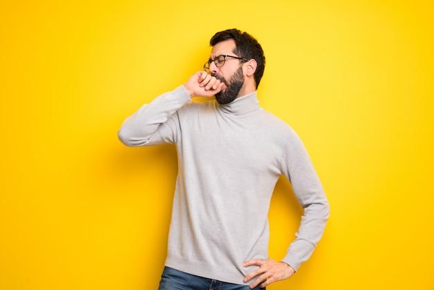 Mann mit bart und rollkragenpullover und offenem mund mit der hand gähnend Premium Fotos