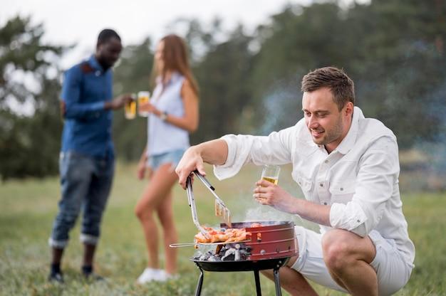 Mann mit bier beim grillen für freunde Kostenlose Fotos