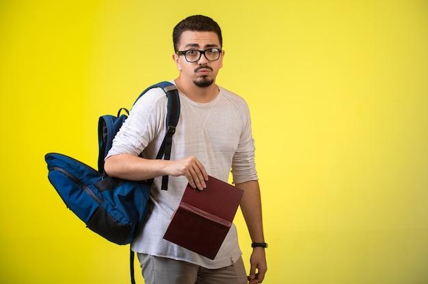 Mann mit brille hält ein buch. Kostenlose Fotos