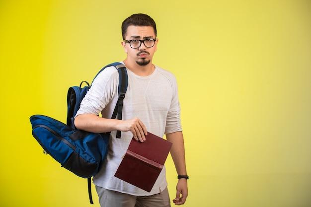 Mann mit brille, rucksack und buch. Kostenlose Fotos