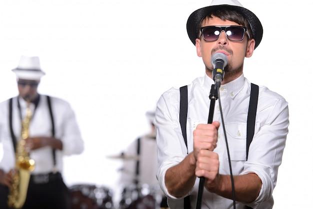 Mann mit brille und mütze steht in der nähe von mikrofon und singt. Premium Fotos