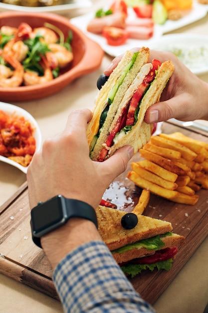 Mann mit club sandwich in den händen von einem esstisch. Kostenlose Fotos