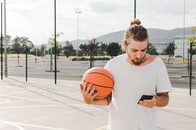Mann mit dem backetball, der vor gericht handy betrachtet Kostenlose Fotos