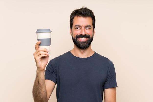 Mann mit dem bart, der einen kaffee mit glücklichem ausdruck anhält Premium Fotos