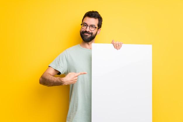 Mann mit dem bart und grünem hemd, die ein leeres plakat für einfügen ein konzept halten Premium Fotos