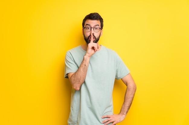 Mann mit dem bart und grünem hemd, die ein zeichen der ruhegeste zeigt, die finger in mund setzt Premium Fotos
