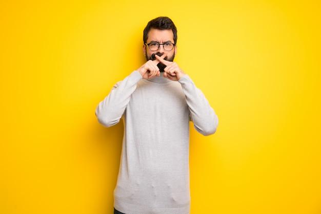 Mann mit dem bart und rollkragenpullover, die ein zeichen der ruhegeste zeigen Premium Fotos