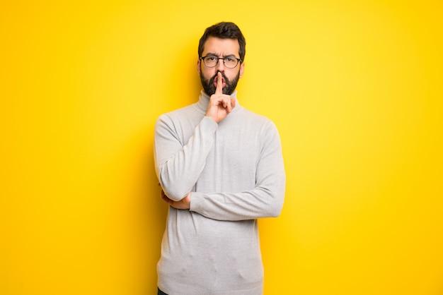 Mann mit dem bart und rollkragenpullover, die ein zeichen der ruhegeste zeigt, die finger in mund setzt Premium Fotos