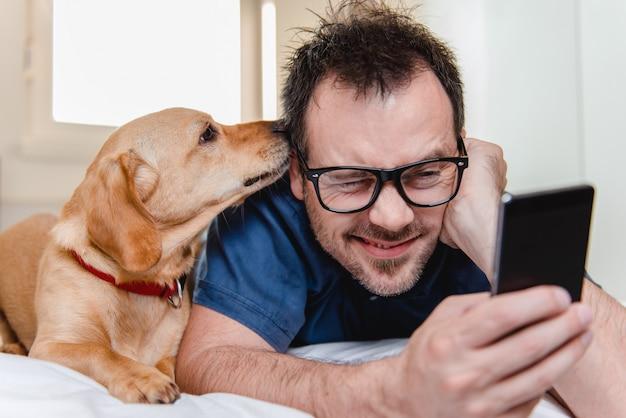 Mann mit dem hund, der intelligentes telefon auf dem bett verwendet Premium Fotos