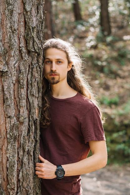Mann mit dem langen haar, das einen baum umarmt Kostenlose Fotos