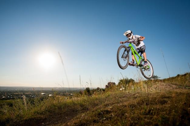 Mann mit dem mountainbike fahren und vom hügel springen Premium Fotos
