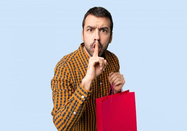 Mann mit den einkaufstaschen, die ein zeichen der ruhegeste zeigen, die finger in mund auf lokalisierten blauen hintergrund einsetzt Premium Fotos