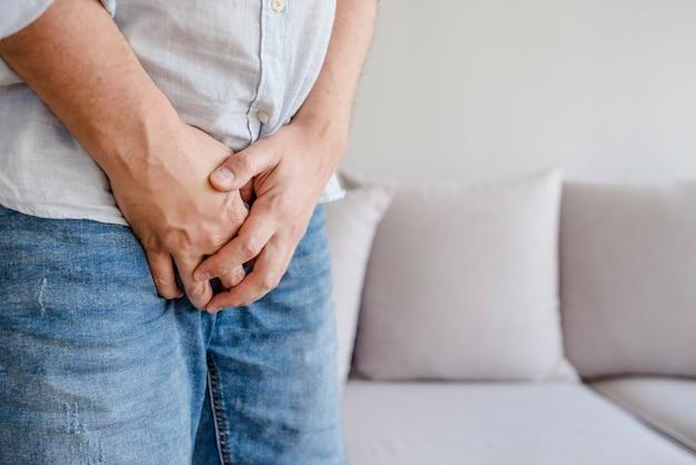 Mann mit den händen, die seine gabelung halten, will er pinkeln - urinausscheidendes inkontinenzkonzept Premium Fotos