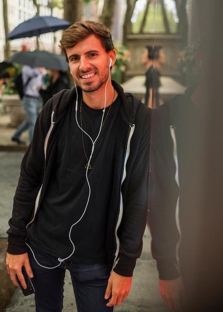 Mann mit den kopfhörern, die an einer wand sich lehnen Kostenlose Fotos