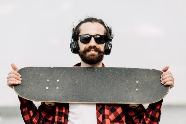Mann mit den kopfhörern, die skateboard halten Kostenlose Fotos