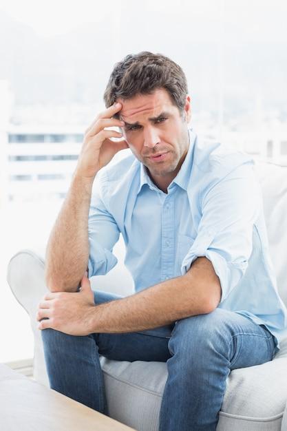 Mann mit den kopfschmerzen, die auf der couch betrachtet kamera sitzen Premium Fotos