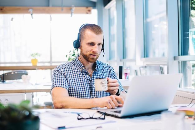 Mann mit der schale und headsetworking auf laptop Kostenlose Fotos
