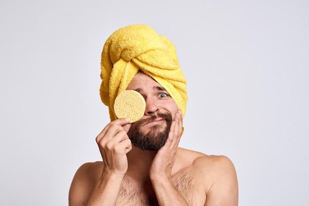 Mann mit einem gelben handtuch auf seinem kopf nackten schultern schwamm saubere haut gesichtspflege licht. Premium Fotos