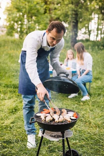 Mann mit einem grill in der natur Kostenlose Fotos