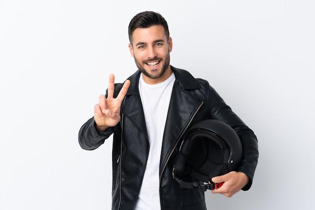 Mann mit einem motorradsturzhelm lächelnd und siegeszeichen zeigend Premium Fotos