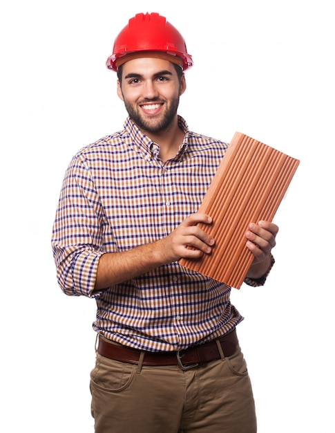 Mann mit einem roten helm und einem ziegelstein Kostenlose Fotos