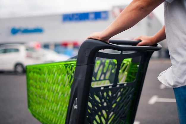 Mann mit einem supermarktwagen auf dem parkplatz Premium Fotos