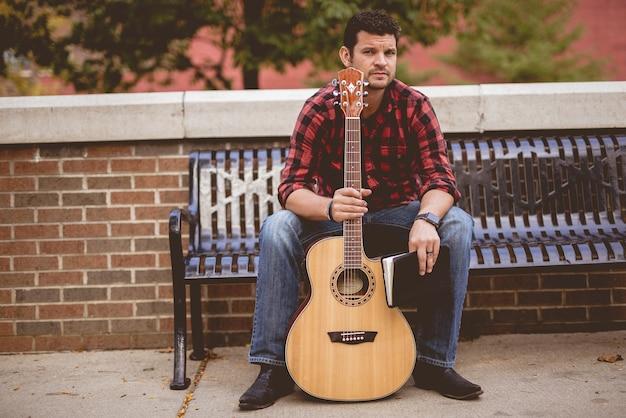Mann mit einer gitarre und einem buch, die auf einer bank im park unter sonnenlicht sitzen Kostenlose Fotos